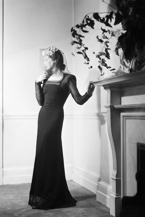 A model wear a black dinner frock by fashion designer Peter Russell.  The dress has a fish net back, arms and hem.