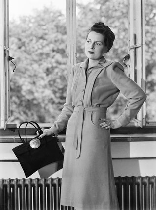 A model leans against a window sill as she shows off her mustard-coloured wool Spectator dress, costing 11 coupons.  She is also wearing a dark-coloured turban and holding a handbag with a large metal clasp.