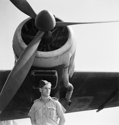 A relaxed portrait of a corporal of the Royal Air Force as he stands under the port engine of Consolidated Liberator Mark II, AL511 'A', of No. 108 Squadron RAF at Fayid, Egypt.  This aircraft is decorated with 'Dumbo' nose art.