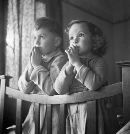 Five year old Andrew and three year old Jacqueline say their prayers before settling down to sleep at the house in which they are staying, somewhere in Surrey.