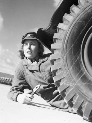 A member of the ATS, pliers in hand, lies on the ground next to the wheel of a lorry or truck, as she prepares to change the wheel as part of her training.  It is possible that this photograph was taken at the training centre at Camberley, Surrey.