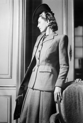 A model wears a brown and beige all-wool checked suit by fashion designer Hardy Amies.  She is wearing a matching coat.  An angled hat completes the outfit.