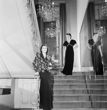 Two models pose for the camera on a staircase at the fashion house of designer Norman Hartnell.  At the top of the stairs, the model wears a black velvet dinner gown studded in blue and gold.  In the foreground, the model wears a dinner suit with the jack