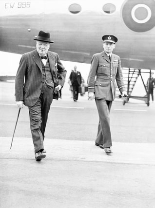 The Prime Minister, Winston Churchill, accompanied by Air Marshal the Hon. Sir Ralph Cochrane, Air Officer Commanding in Chief, Transport Command, walks from his Douglas Skymaster Mark I, EW999, at Northolt, Middlesex, on his return from the Three Power C