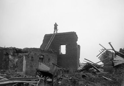 An artillery observation officer on top of a ruined wall at Havrincourt.