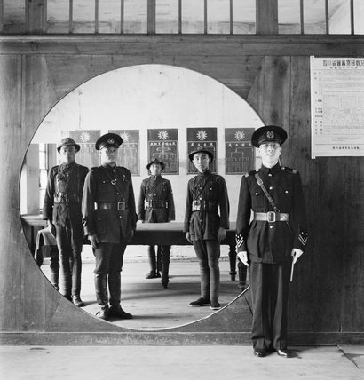 The Chinese Police Force; the Assistant Chief of Police and his staff grouped in a circular doorway at headquarters in Chengtu.