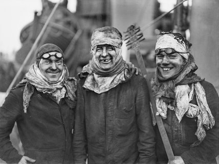 A group of smiling boiler cleaners taking a breather on the deck of a destroyer. They are men of the Royal Navy who do very dirty work but are seldom heard of. Their work is carried out during the short period that a ship is in harbour.