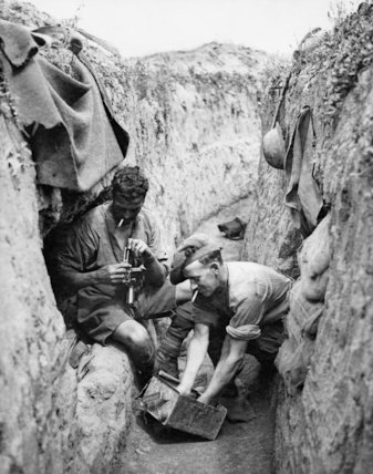 Two Canadian soldiers clean a Lewis Gun in a reserve trench during the Third Battle of Ypres (Passchendaele), November 1917.