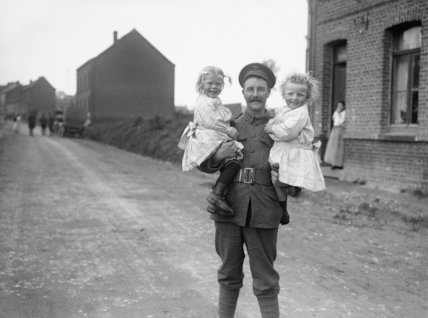 A soldier of the 15th Battalion, London Regiment (Civil Service Rifles) with French children in Bruay-en-Artois, 11th June 1916.