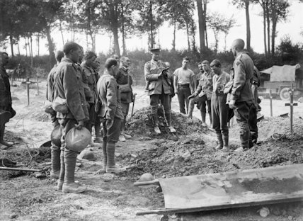 Other ranks stand to attention as an officer reads from the Bible at the funeral of an Australian soldier, Becourt Wood, Somme, August 1916.