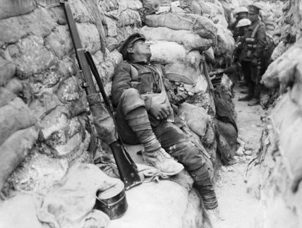 An exhausted soldier asleep in a front line trench at Thiepval, Somme, September 1916.