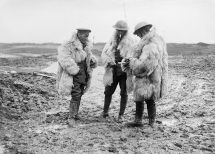 Three British troops smoking, and wearing thick, long-haired sheepskin coats, 7 August 1916.