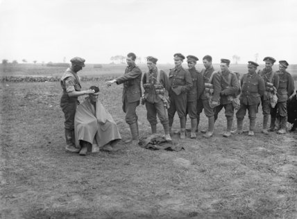 Troops of the 1/5th Battalion, Northumberland Fusiliers waiting for their turn for a hair cut. Toutencourt, October 1916.