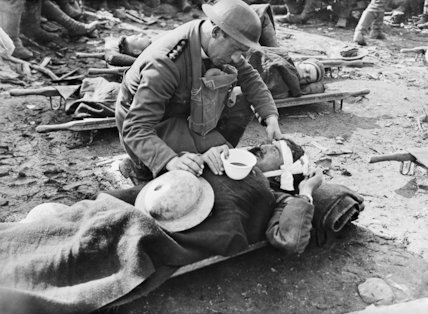 A padre gives a drink to a badly wounded soldier near Potijze.