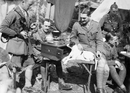 Tank officers relaxing around a gramophone player, with their pet dogs, in camp at Poperinghe.