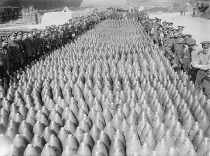 British soldiers stand around the edge of a large collection of shells at a shell dump at Contay.