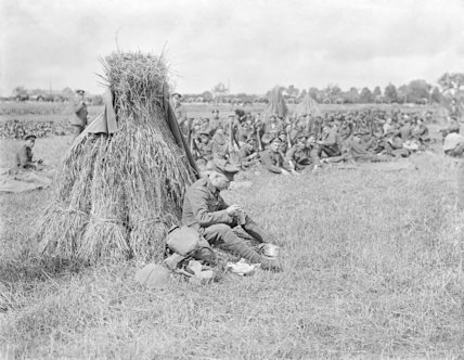 A Sergeant Major of the 16th Irish Division having a breakfast meal by a wheatsheaf. The Amiens - Albert Road, 25th August 1916.