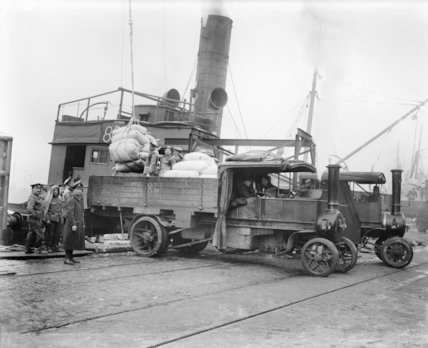 British troops unloading flour from a ship on to steam wagons. Calais, March 1917.