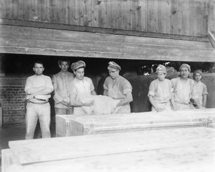 Taking the dough out of the bins to be made into loaves. Army bakery, Calais, March 1917.