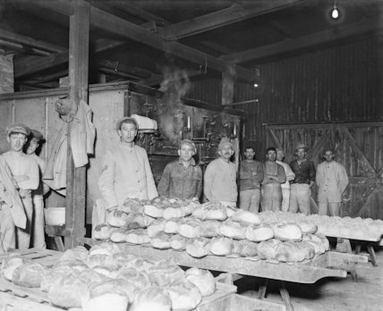 One of the ovens with newly baked bread. Army bakery, Calais, March 1917.