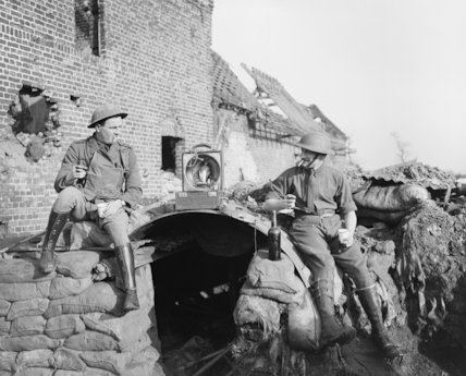British officers enjoying a drink and music from a gramophone outside their elephant-back shelter at Givenchy, 28 January 1918.