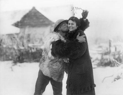 Man of the Machine Gun Corps in sheepskin coat kissing French farm-girl under mistletoe. Near Hesdin, 20 December 1917.
