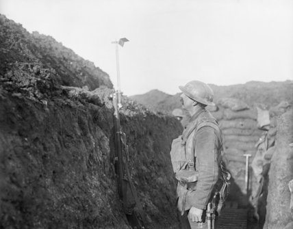A soldier of the York and Lancaster Regiment uses a mirror periscope attached to his bayonet to look over the top of a trench. Oppy, Pas-de-Calais, 12 January 1918