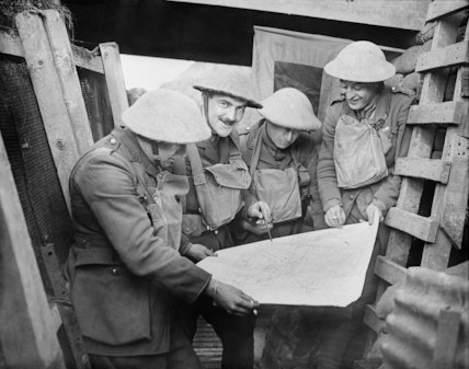 Officers of the 6th York and Lancaster Regiment consulting a map in a trench. Cambrin, 6 February, 1918.