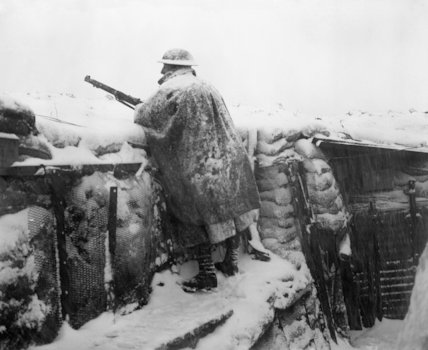 A sentry of the 12th East Yorkshires on the fire step of a snow-covered trench. He is wearing a mackintosh cape over his greatcoat. Near Roclincourt. 9 January 1918.