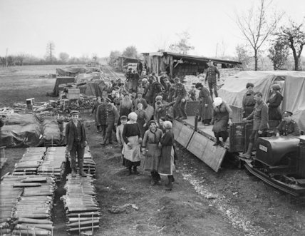 Italian girl workers detraining from light railway trucks at a railhead ammunition dump.