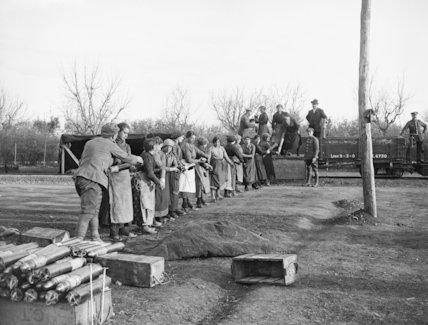 Italian girls loading 18 pdr shells on to railway trucks.