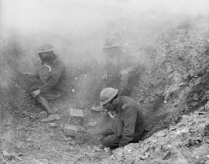 Men of the R. G. A. wearing gas masks, operating a Fullerphone in a shell hole, forward signal post.