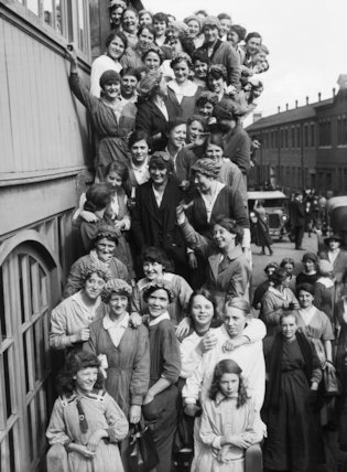A large group of women workers smile and wave for the camera as they crowd down the steps outside an aeroplane factory in Birmingham.