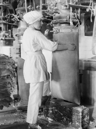 Woman worker filling sacks with Government flour in the mills of Messes. Rank & Sons, Birkenhead, September 1918.