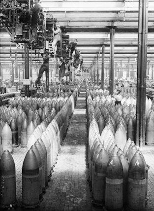 'Crane girls' at work at the National Filling Factory, Chilwell. They can be seen hanging down from cranes above rows of shells.