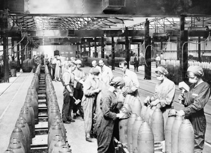 Men and women use wooden mallets to secure the tops of shells in the 'Melting House' of the National Filling Factory, Chilwell.