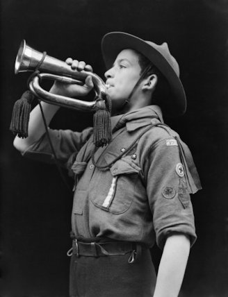 A portrait of a Boy Scout bugler as he sounds the 'all clear' after an air raid.
