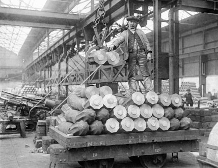 Billets of metal are loaded for transportation by winch at a National Projectile Factory.