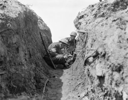 Signalman crouching in a trench.