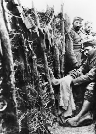 A German soldier washes his feet in a trench in preparation for an inspection.