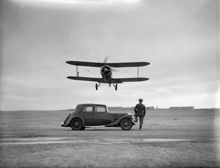 A Gloster Gladiator of No. 521 Squadron RAF takes off over a four-door saloon car at Bircham Newton, Norfolk.