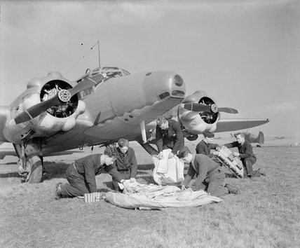 Ground crew packing a dinghy and its supplies for installation in an Avro Anson Mark I