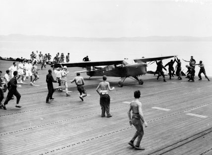 The handling party nearing the Auster as it runs up the flight deck