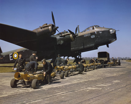 Royal Air Force armourers check over the sixteen 250lb bombs before they are loaded into Short Stirling bomber N6101 of No