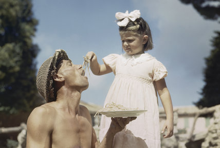 A little girl feeds a soldier with macaroni.