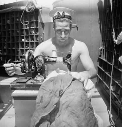A British sailor uses a sewing machine to repair a signal flag on board the armed merchant cruiser HMS ALCANTARA en route to Sierra Leone, 1942