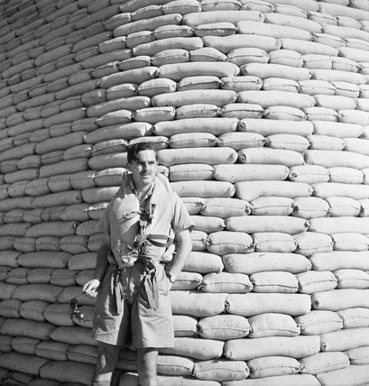 An airman poses in front of a sandbagged aircraft revetment, RAF Shallufa, Egypt, 1942