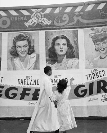 A Hollywood film poster attracts the attention of local Egyptians, Cairo, Egypt, 1942