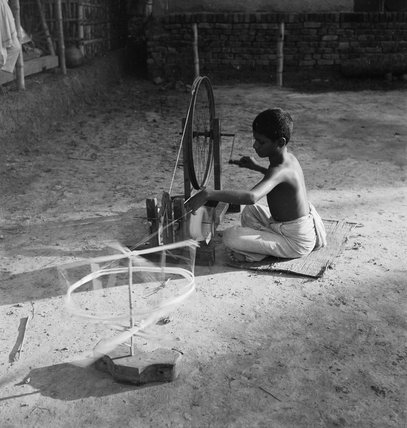 IN A BENGALI VILLAGE:  A SCHOOLBOY AT A SPINNING WHEEL OUTSIDE THE SCHOOL