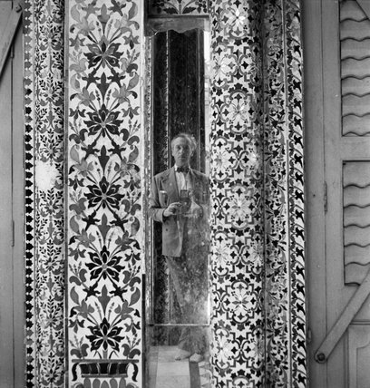 Cecil Beaton reflected in an ornamental mirror in the Parshwanath Jain Temple, Calcutta, India, 1944